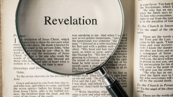 open bible to the book of revelation with a magnifying glass on top